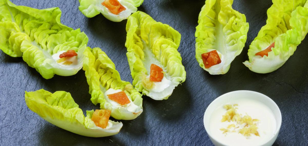 Feuille de salade à la sauce blanche, aromatisée à l'ail et au gingembre frais, accompagnée de mini-crackers